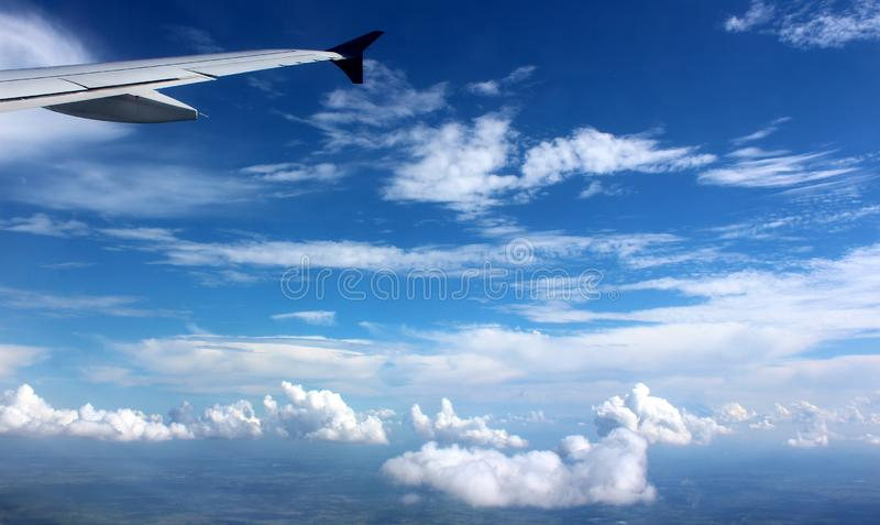 Periwinkle blue skies with white puffy clouds moving across the surface seen from window of plane with small part of wing. Scene from the window of a jet liner stock image