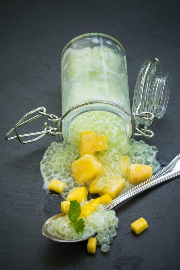 Perlas del sagú en leche de coco con el mango imagen de archivo