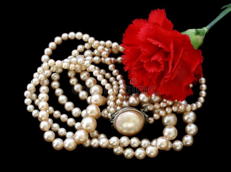 Perlas rosadas de la vendimia y coche rojo imagen de archivo