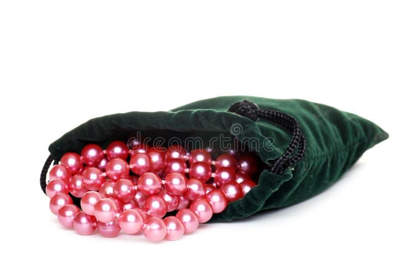 Perlas rosadas en un bolso verde fotografía de archivo libre de regalías
