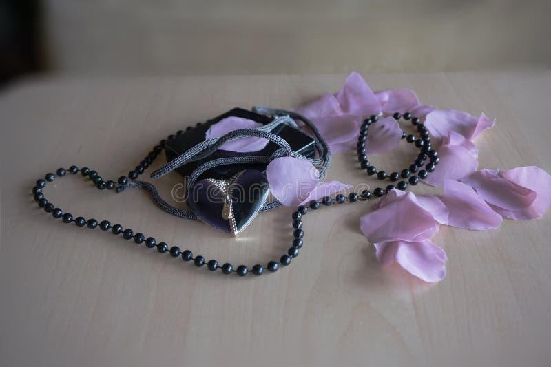 Perle des feuilles de roses avec le coeur sur le tabel photo stock