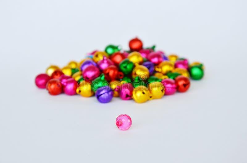 Perle en plastique rose et cloche colorée sur le fond blanc photos stock