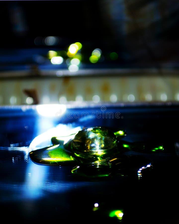 Perle en verre avec de l'huile colorée avec la réflexion de bokah dans le miroir image libre de droits
