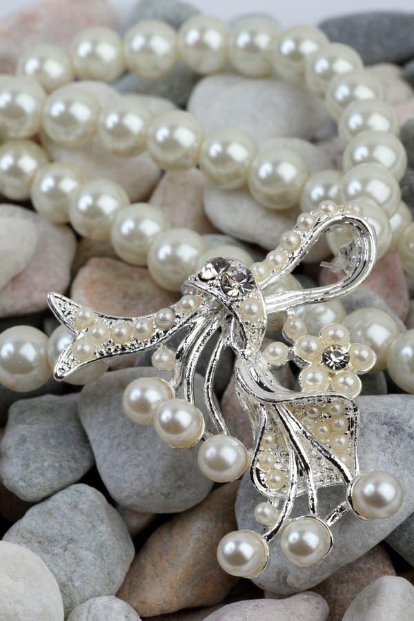 Perle jewelery auf Steinen lizenzfreie stockbilder