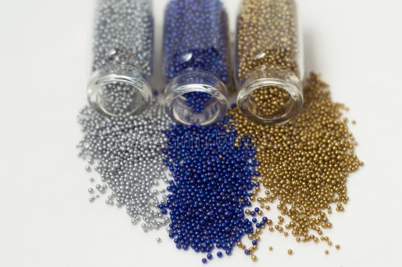 Perle multicolori in barattoli di vetro Le perle sono versate su un fondo bianco Di polimeri colorati multi di plastica Pillets d fotografia stock libera da diritti