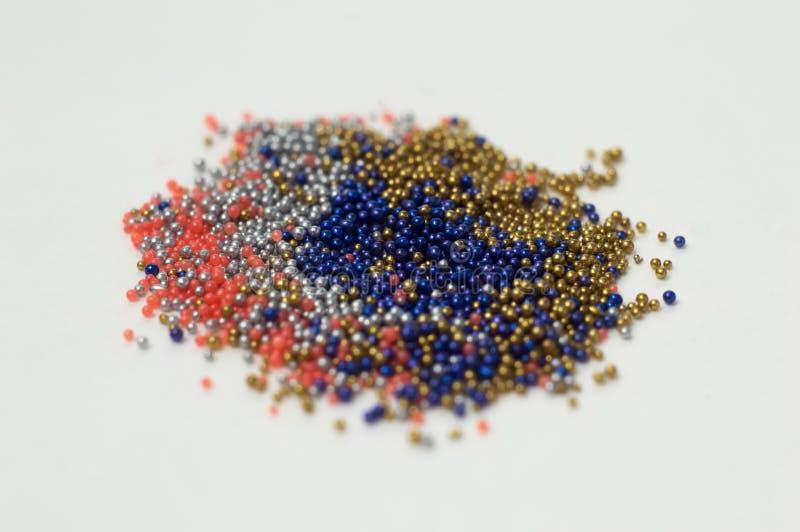 Perle multicolori in barattoli di vetro Le perle sono versate su un fondo bianco Di polimeri colorati multi di plastica Pillets d immagini stock libere da diritti
