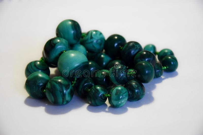 Perle naturali della malachite su un fondo bianco immagine stock libera da diritti