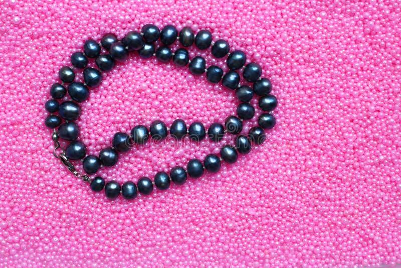 Perle nere della perla su fondo rosa, spazio della copia fotografia stock