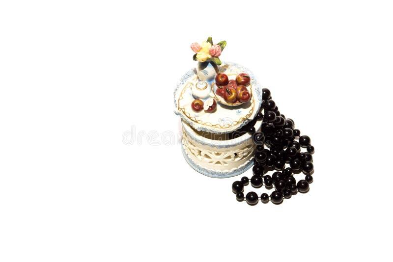 Perle nere e scatola su un fondo bianco fotografia stock
