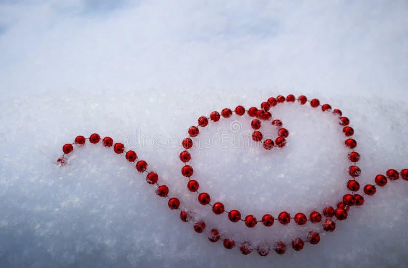Perle rosse luminose nella forma di un cuore su neve bianca fresca Giorno di biglietti di S. Valentino perfetto, Natale, fondo de immagini stock libere da diritti