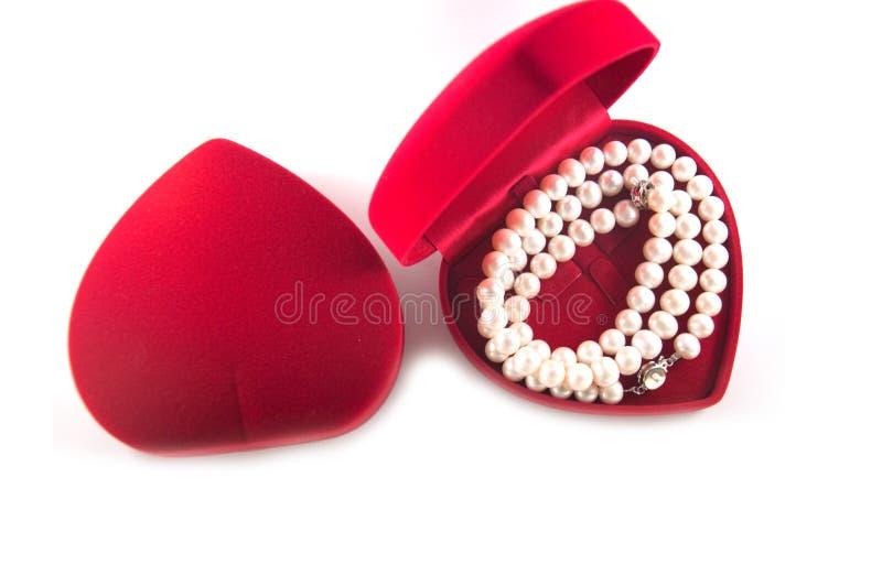 Perle in una scatola rossa a forma di del cuore fotografia stock libera da diritti