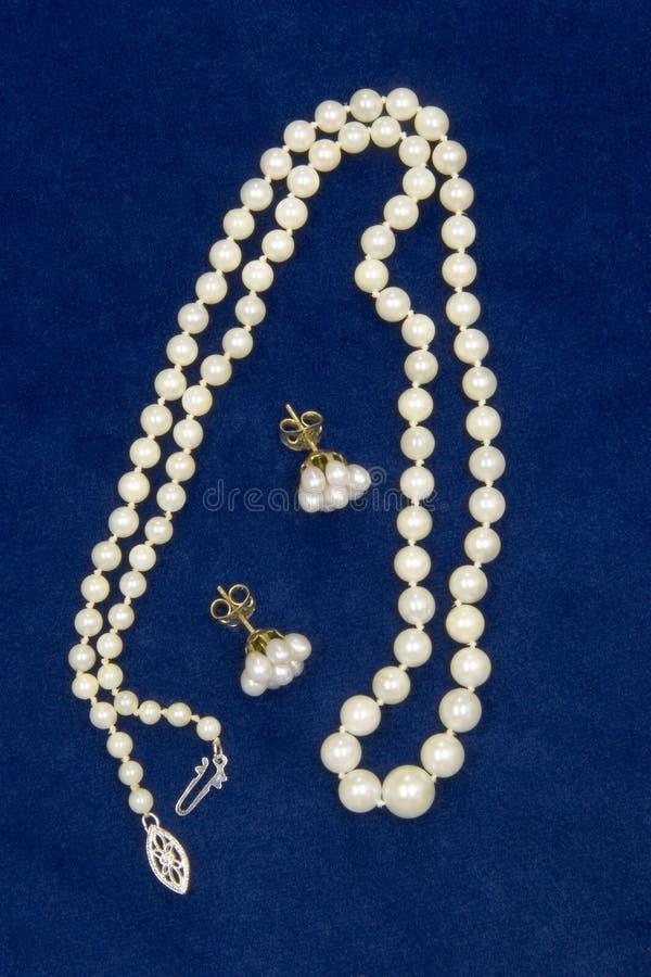 Perlen auf blauem Samt stockfotos