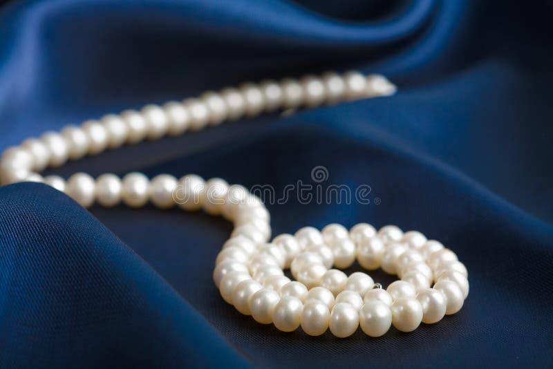 Perlen Sie Halskette über blauer Seide lizenzfreies stockfoto