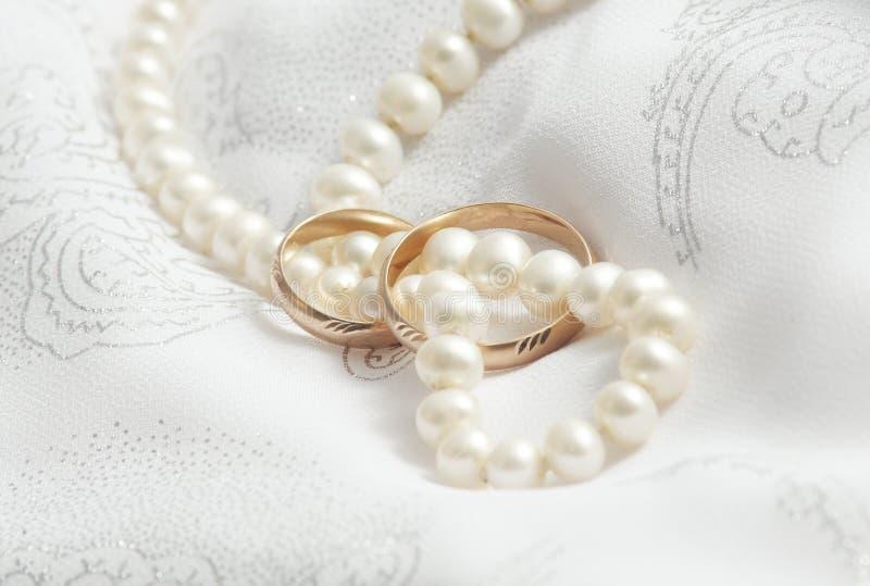 Perlen und Hochzeitsknalle auf einem Gewebe. stockbilder