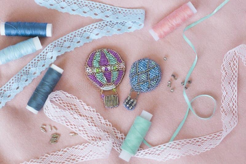 Perlenbesetzte Broschen in Form der montgolfiers oder Ballone mit den Silber-, hellblauen, Grauen, Grünen und violettenperlen und lizenzfreie stockfotografie