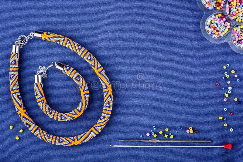 Perlenbesetzte Halskette von farbigen Perlen auf einem blauen Hintergrund Kopieren Sie Platz stockfotografie