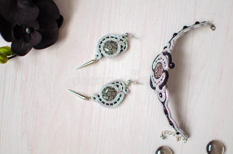 Perlenbesetzter Armband- und Ohrringsatz Silberner grauer soutache Schmuck auf dem weißen hölzernen Hintergrund Frauenzubehör lizenzfreie stockbilder