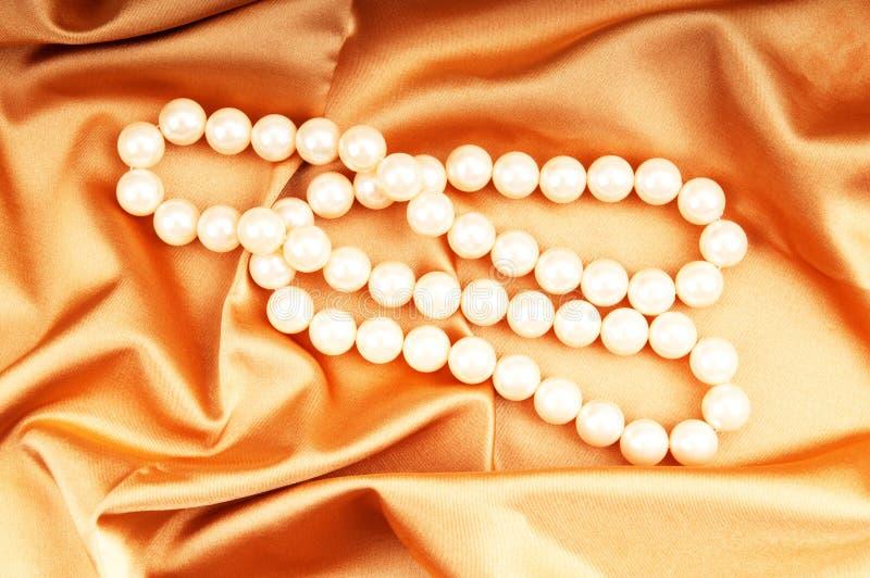Perlenhalskette auf dem hellen Satin stockbild