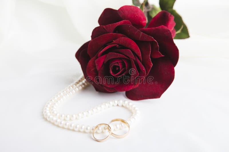 Perlenherz, eine Rose und Eheringe stockfotografie