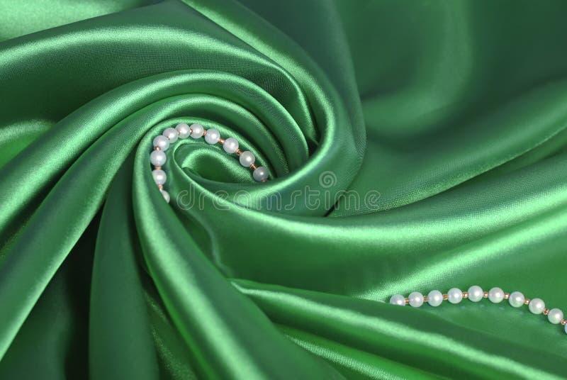 Perlenkorne auf grüner Seide lizenzfreies stockfoto