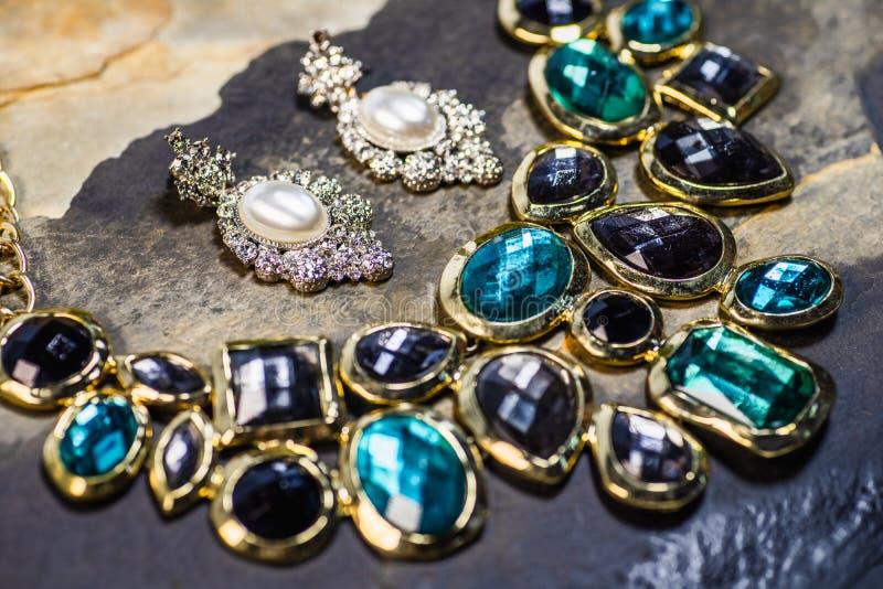 Perlenohrring- und -edelsteinanhänger, traditioneller Schmuck Weiblicher Schmuck der schönen Weinlese auf dunklem Steinhintergrun lizenzfreie stockfotografie