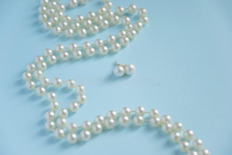 Perles blanches sur le fond bleu - concept de luxe de mode image libre de droits