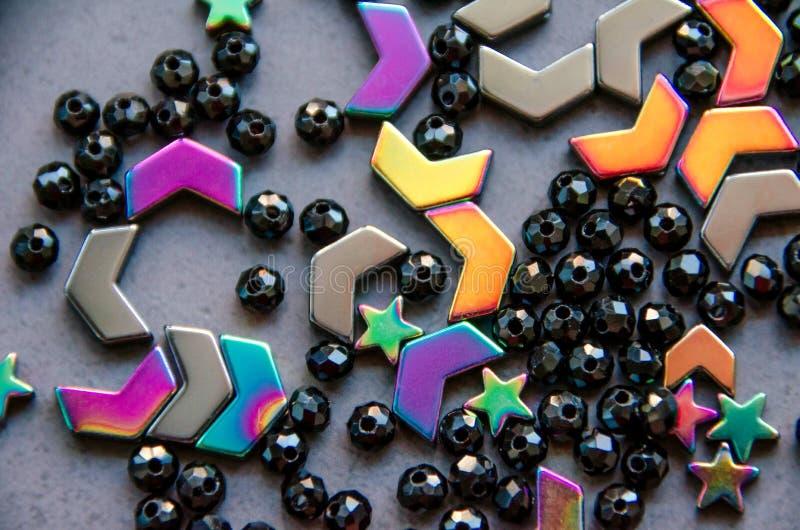 Perles colorées et noires et pierres d'isolement sur le fond gris photos stock