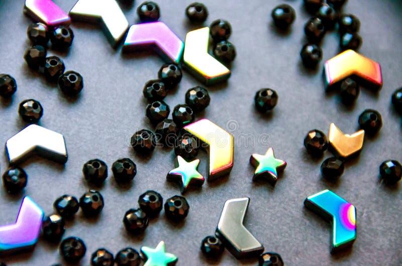 Perles colorées et noires et pierres d'isolement sur le fond gris photo stock