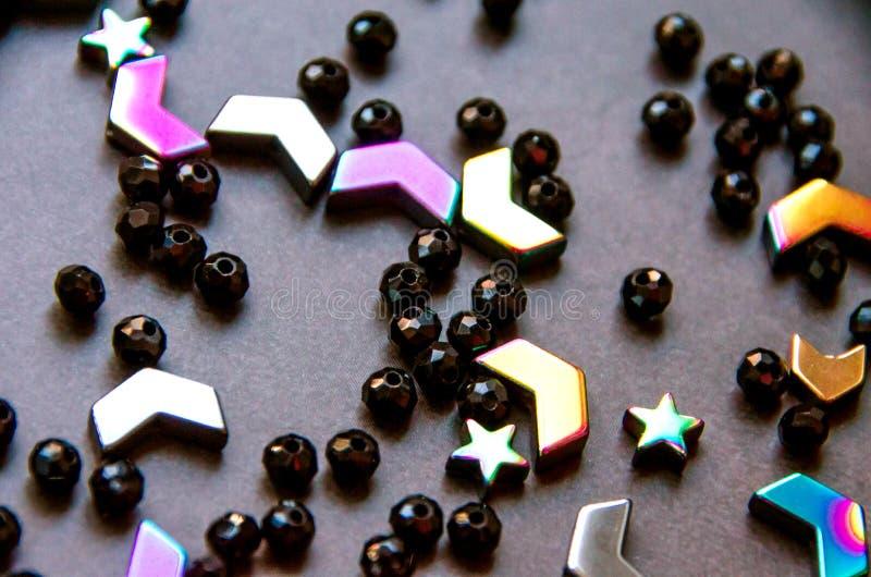 Perles colorées et noires et pierres d'isolement sur le fond gris images stock