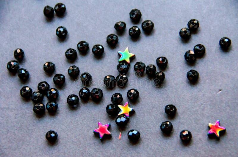 Perles colorées et noires et pierres d'isolement sur le fond gris images libres de droits