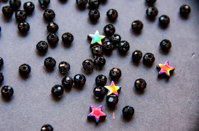 Perles colorées et noires et pierres d'isolement sur le fond gris image libre de droits