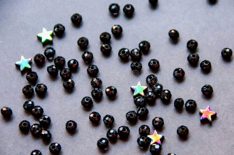 Perles colorées et noires et pierres d'isolement sur le fond gris image stock