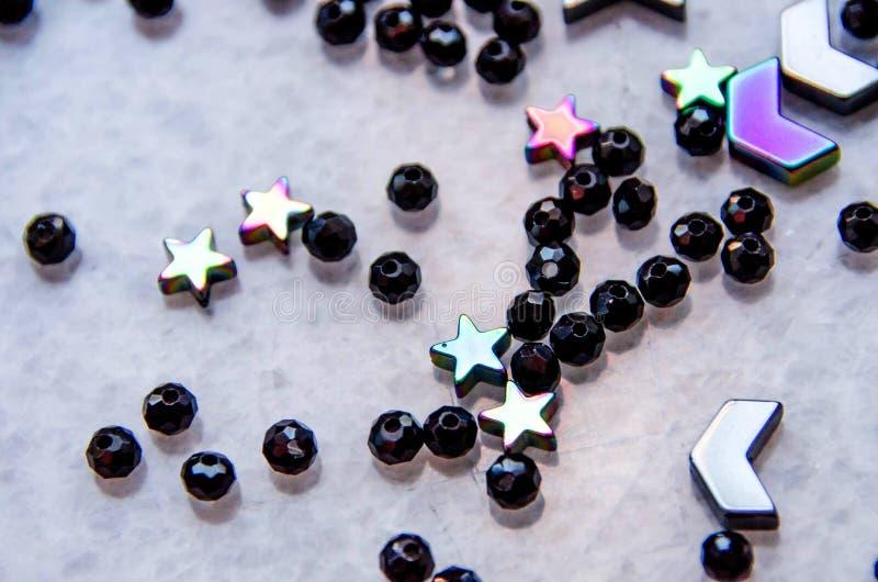 Perles colorées et noires et pierres d'isolement sur le fond gris photos libres de droits