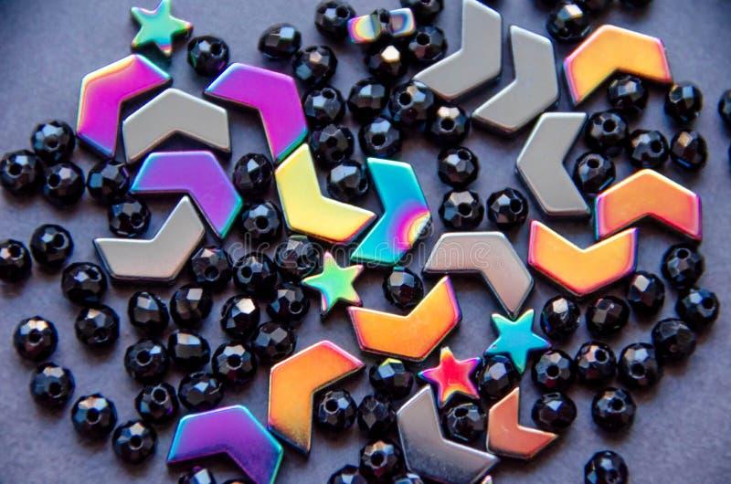 Perles colorées et noires et pierres sur le fond gris images stock