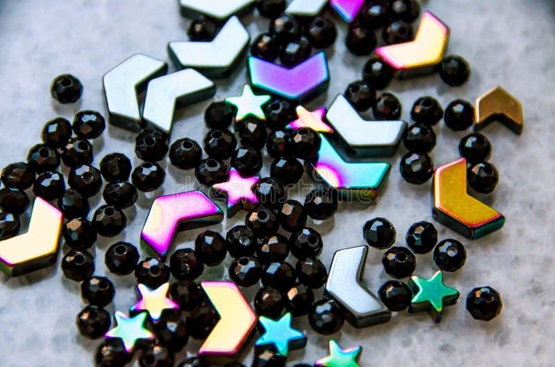 Perles colorées et noires et pierres sur le fond gris photos libres de droits