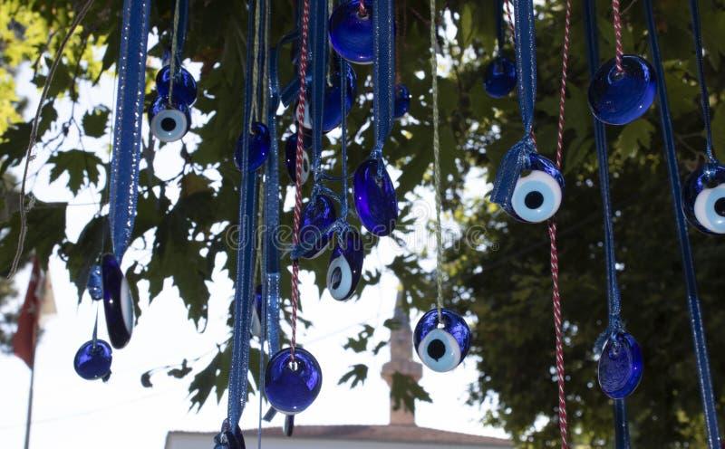 Perles d'oeil mauvais accrochant sur l'arbre photo libre de droits