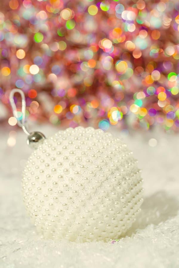 Perles de nacre de boule de No?l sur une neige et un beau fond color? brouill? de bokeh ?clatant avec les lumi?res rougeoyantes O image libre de droits