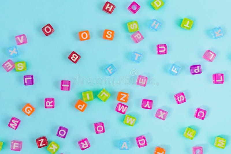 Perles en plastique multicolores de cube avec des lettres dispersées sur le fond bleu Texture de fond d'alphabet photographie stock