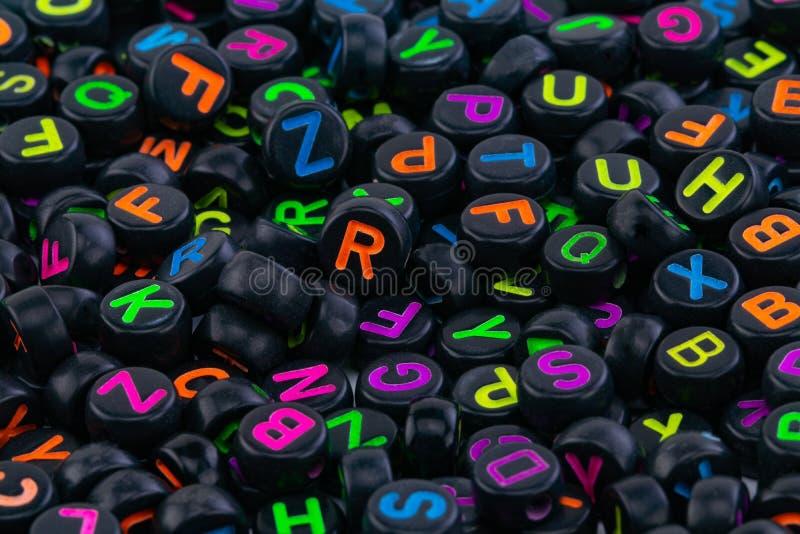 Perles en plastique noires avec les lettres color?es plac?es al?atoirement photographie stock