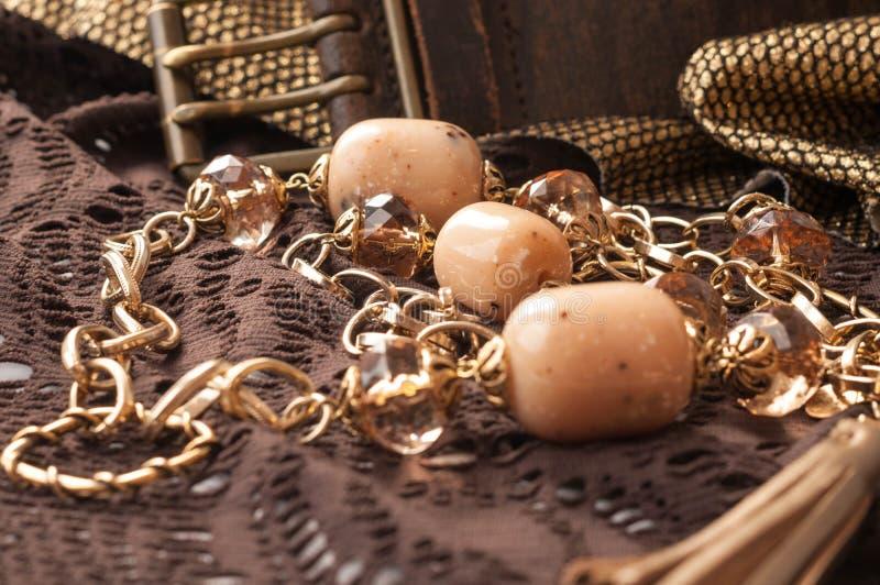perles et chaîne d'or près de la ceinture en cuir sur la dentelle texturisée brune photos stock