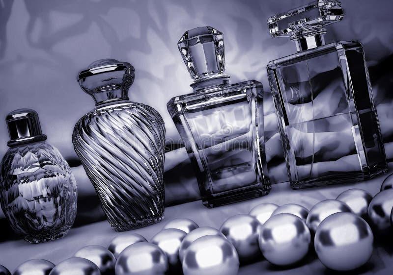 Perles et différentes bouteilles de parfum sur un backgroun gris-foncé image libre de droits