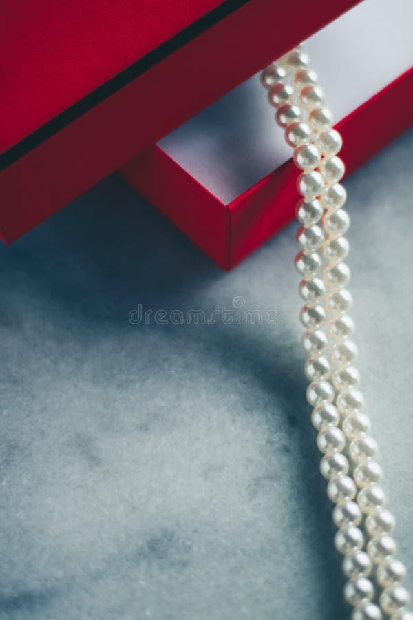 perles merveilleuses dans un boîte-cadeau rouge, un présent luxe - bijoux et un cadeau de luxe pour son concept dénommé photo stock