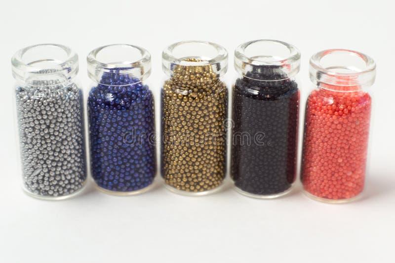 Perles multicolores dans des pots en verre Des perles sont vers?es sur un fond blanc Polym?res multicolores en plastique Pillets  photo stock