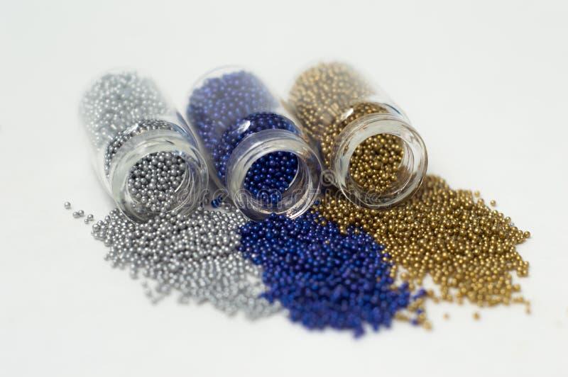 Perles multicolores dans des pots en verre Des perles sont vers?es sur un fond blanc Polym?res multicolores en plastique Pillets  photographie stock