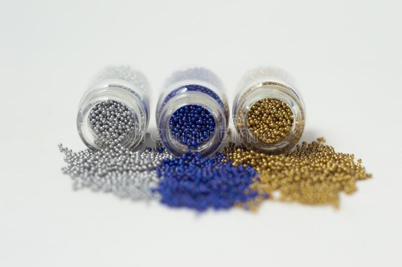 Perles multicolores dans des pots en verre Des perles sont vers?es sur un fond blanc Polym?res multicolores en plastique Pillets  photographie stock libre de droits