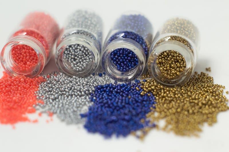 Perles multicolores dans des pots en verre Des perles sont vers?es sur un fond blanc Polym?res multicolores en plastique Pillets  photos libres de droits