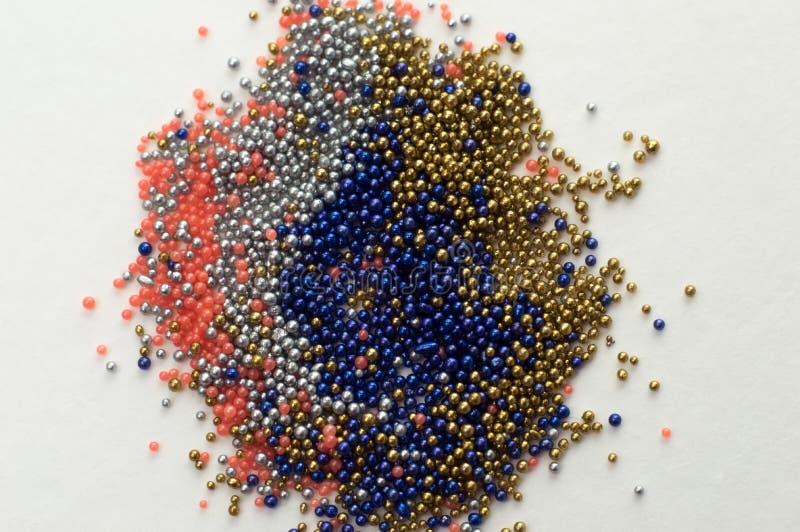 Perles multicolores dans des pots en verre Des perles sont vers?es sur un fond blanc Polym?res multicolores en plastique Pillets  images libres de droits