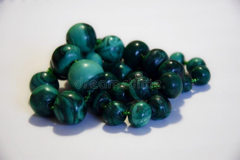 Perles naturelles de malachite sur un fond blanc image libre de droits