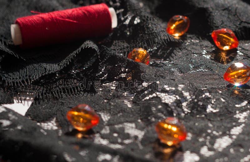 Perles oranges en verre et bobine rouge de fil sur la dentelle noire d'ornement sur le blanc photos stock