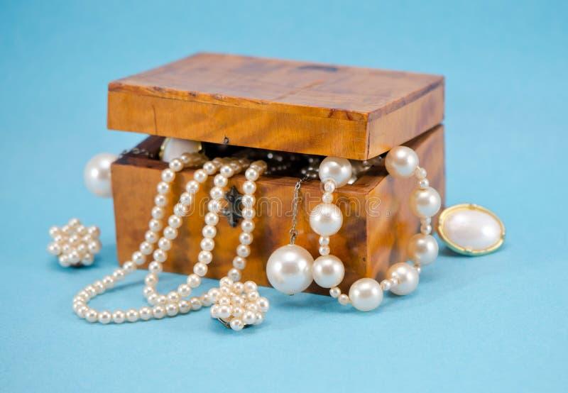 Perlez le defocus de bijou dans le rétro cadre en bois sur le bleu photo stock